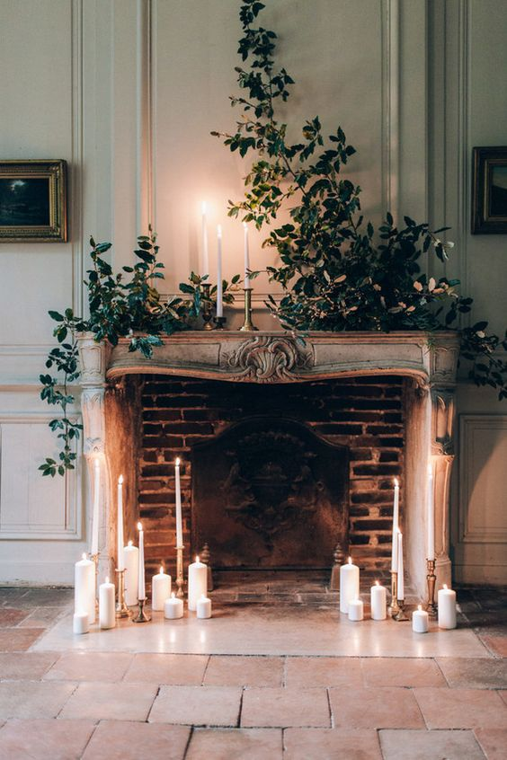a refined fireplace with lush greenery and candles all around will become a perfect wedding backdrop
