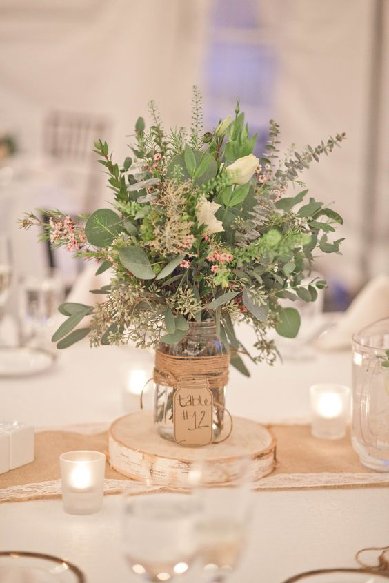 a textural rustic centerpiece of various foliage and some white blooms, the jar is wrapped with twine and a tag