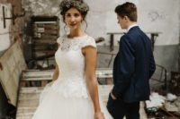 an A-line wedding dress with a lace bodice, cap sleeves, an illusion neckline and a layered tulle skirt