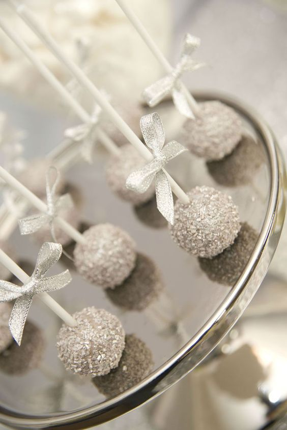silver glitter cake pops with silver bows are a great winter wedding dessert that is original at the same time