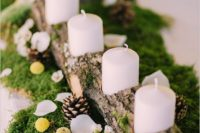 27 a cozy rustic centerpiece of moss, pinecones, petals, billy balls and a wood stummp with candles