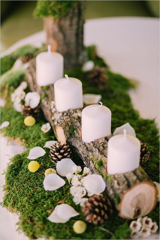 a cozy rustic centerpiece of moss, pinecones, petals, billy balls and a wood stummp with candles