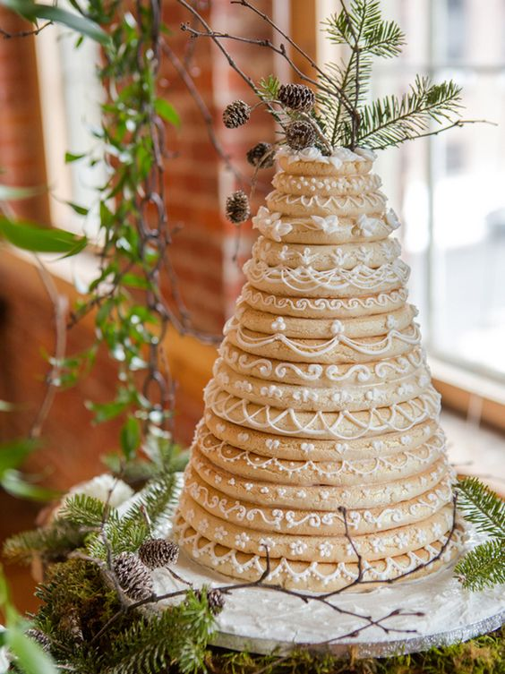 a traditional Iceland wedding cake called kransakaka topped with real evergreens and pinecones