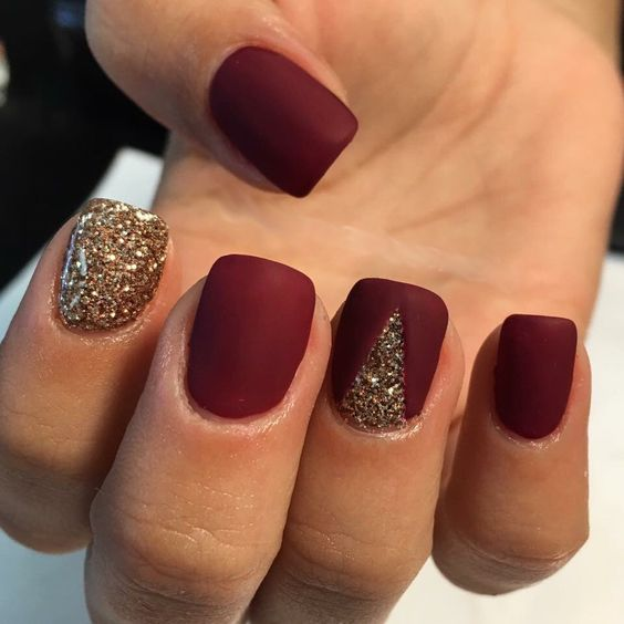 matte burgundy nails with a touch of gold glitter and a gold glitter nail for a bright festive manicure in winter