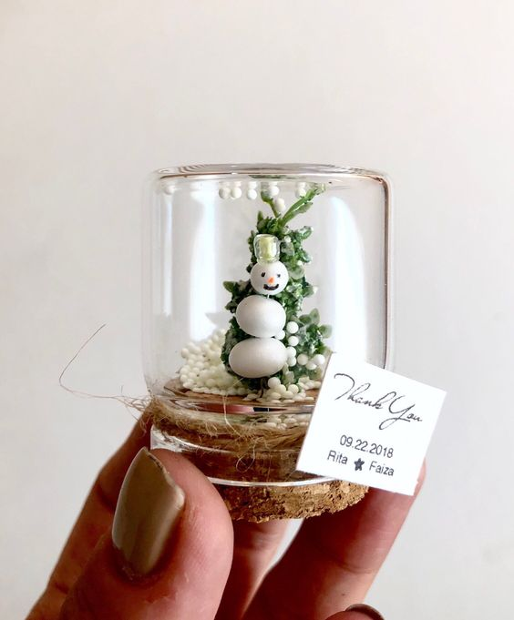 tiny jar favors with a fake snowman and a fake Christmas tree, such a mini terrarium is super cute