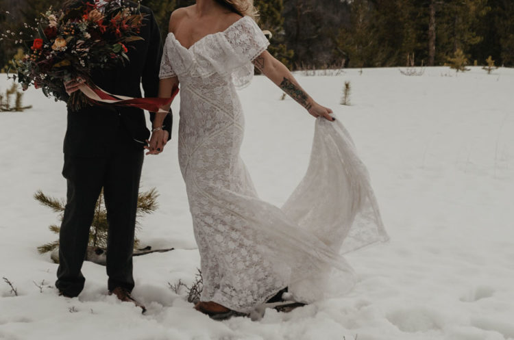 The bride was wearing an off the shoulder boho lace wedding dress and boots
