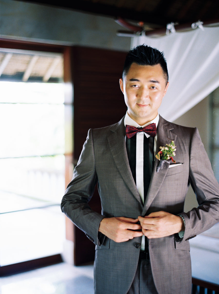 The groom was wearing a grey suit, a striped shirt and a burgundy bow tie