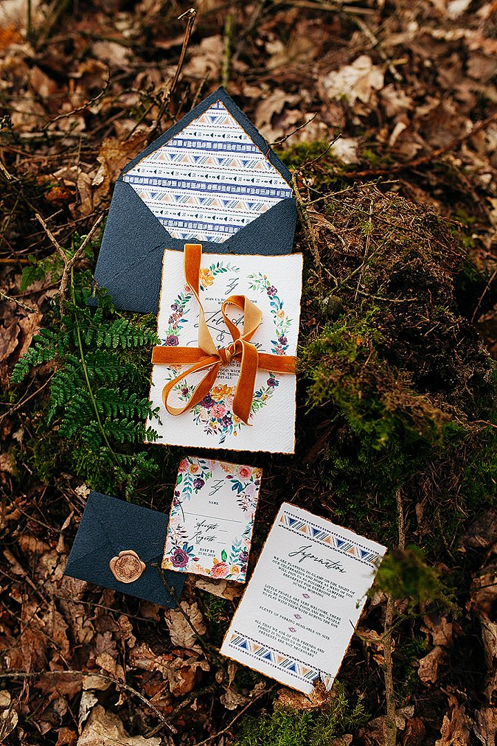 The wedding invitation suite was done with bright hand painted florals, colorful ribbons and a raw hem