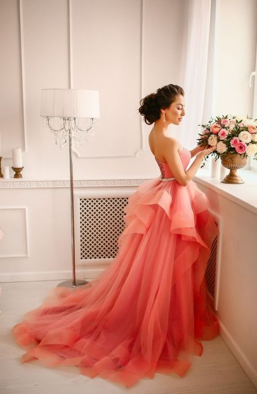 a coral ballgown with an embellished belt and a layered skirt with a train is a daring choice for 2019 bride