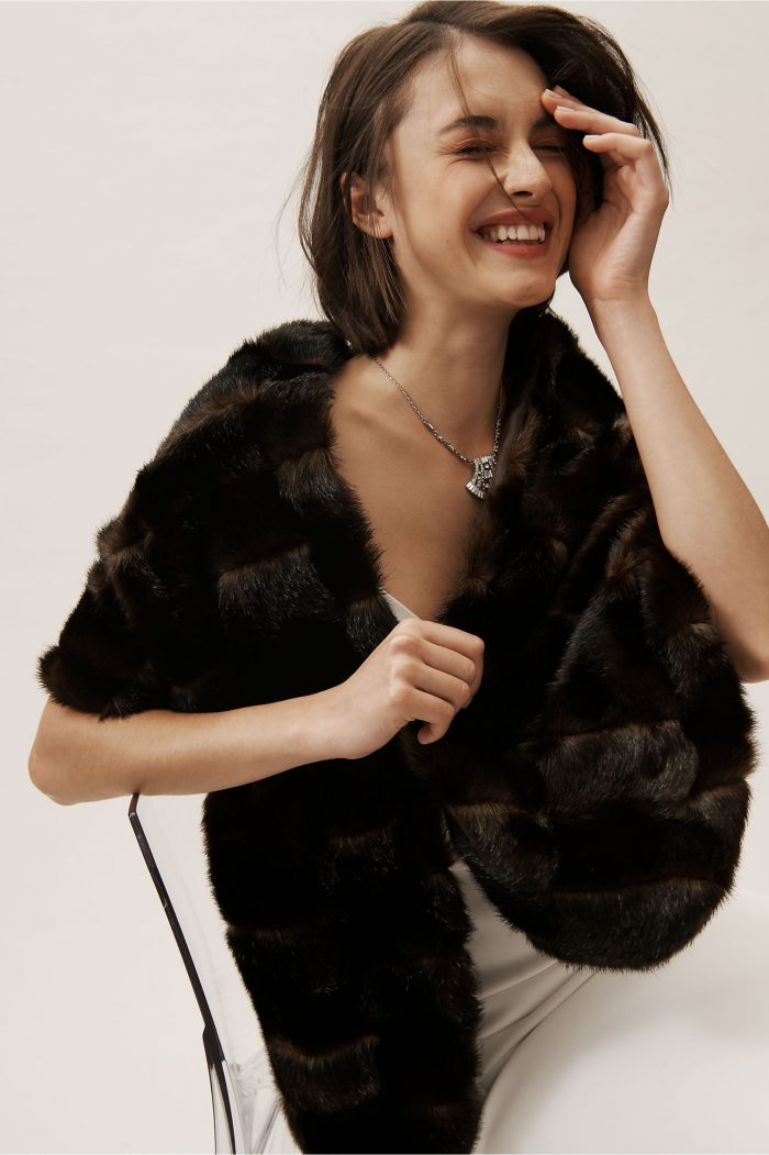 a dark fur shrug will contrast your wedding dress, make you stand out in the snow and it looks luxurious
