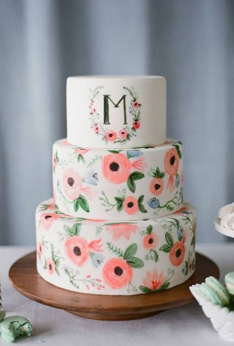 a fun handpainted wedding cake in bold coral with a primitivist touch, a large monogram on the top tier