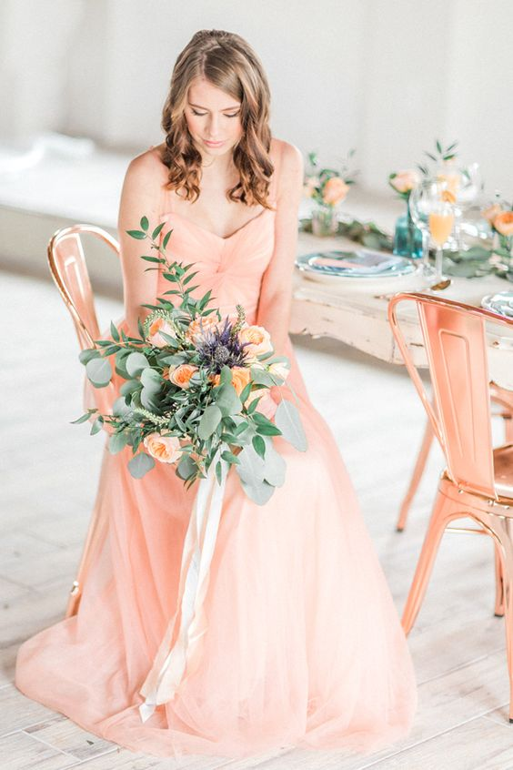 a gorgeous spaghetti strap peachy wedding dress with drapings and a peachy wedding bouquet