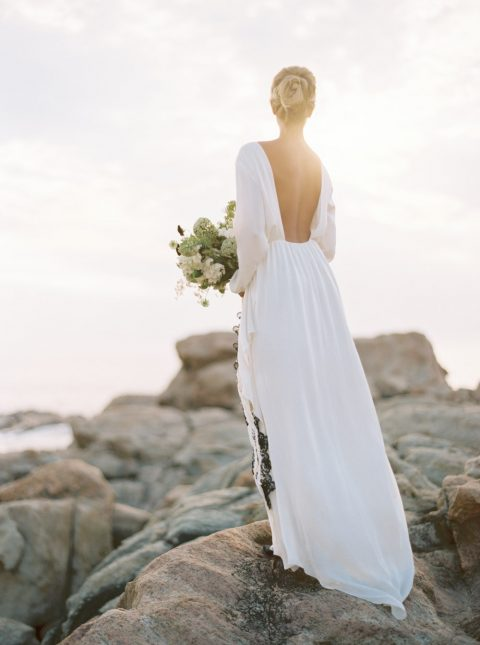 an airy and flowy wedding gown with an open back and long sleeves is a cool modern idea