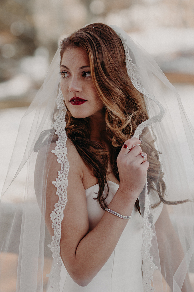 She added a veil with a lace and some stylish accessories, a red lip and matching nails to achieve a chic look