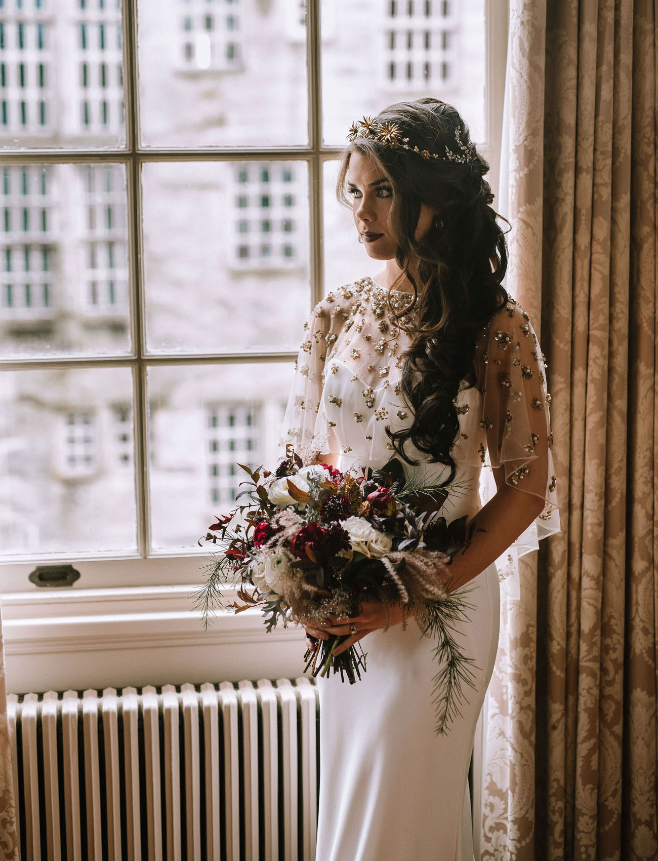 The bride was wearing a fitting modern wedding gown with an embellished shawl, long wavy hair and a dark lip
