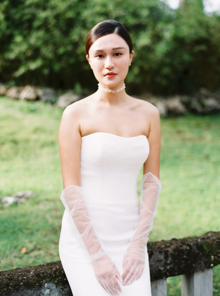 The bride was wearing a modern strapless fitting wedding dress, an airy choker with pearls, tulle gloves and earrings