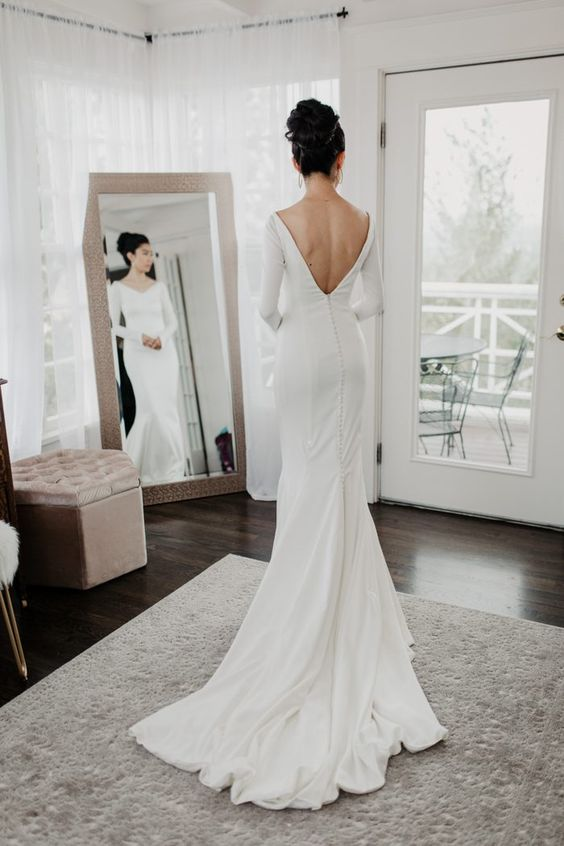a chic modern wedding gown with a V neckline and a cutout back on buttons, long sleeves and a train