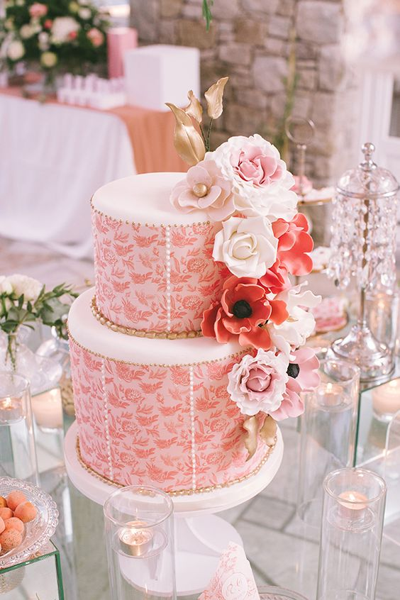 a gorgeous wedding cake in coral and white, with gold and blush sugar blooms on top