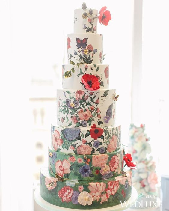 an oversized wedding cake with white and green tiers, with handpainted flowers and sugar blooms is a gorgeous statement