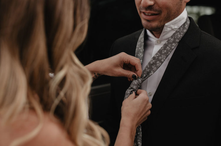The groom was wearing a black suit with a floral print tie in grey