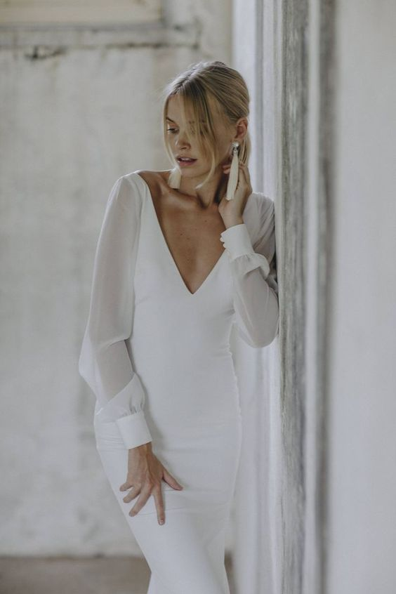 a modern and elegant wedding dress with a fitting silhouette, a plunging neckline, long sleeves and tassel earrings