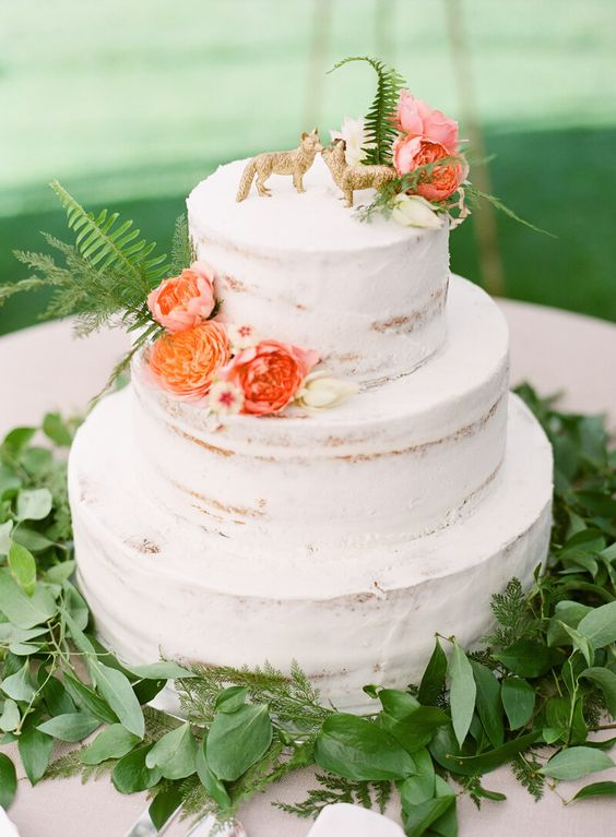 a naked wedding cake with coral blooms, ferns and gilded fox toppers is a great and fresh summer idea