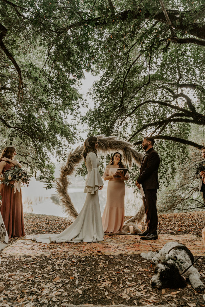 The wedding ceremony space was done with a trendy wreath wedding arch of pampas grass and boho rugs