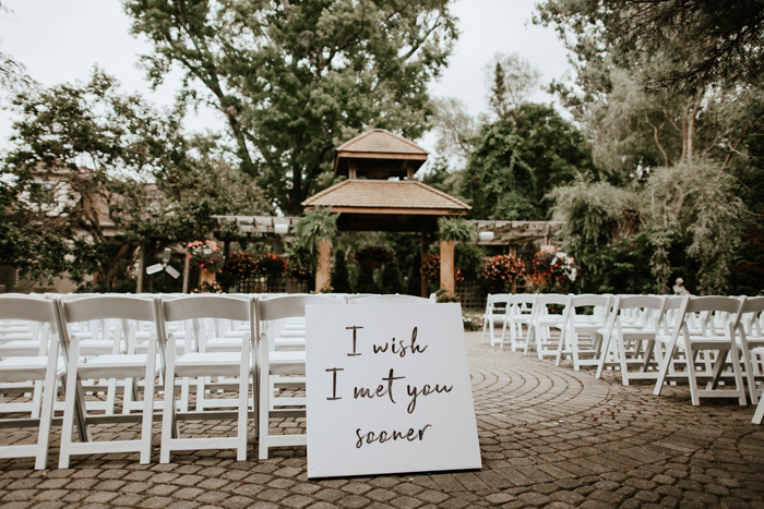 The wedding ceremony space was set in the garden, there was a single sign to decorate the aisle