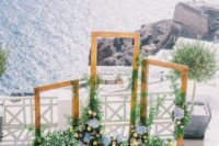 05 a beautiful Mediterranean wedding ceremony space with several frames and lush blooms and greenery around plus a sea view