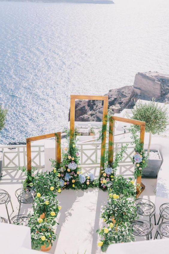 a beautiful Mediterranean wedding ceremony space with several frames and lush blooms and greenery around plus a sea view
