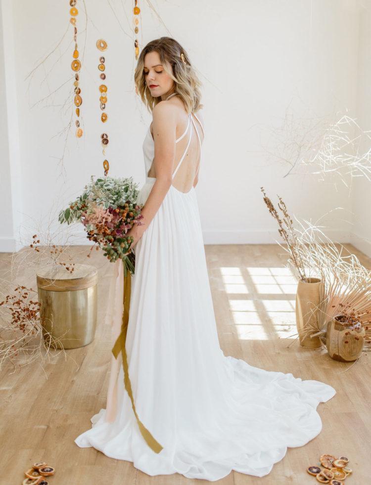 a modern plain wedding dress with a cutout back, a train and a high neckline is great for a Scandinavian bride