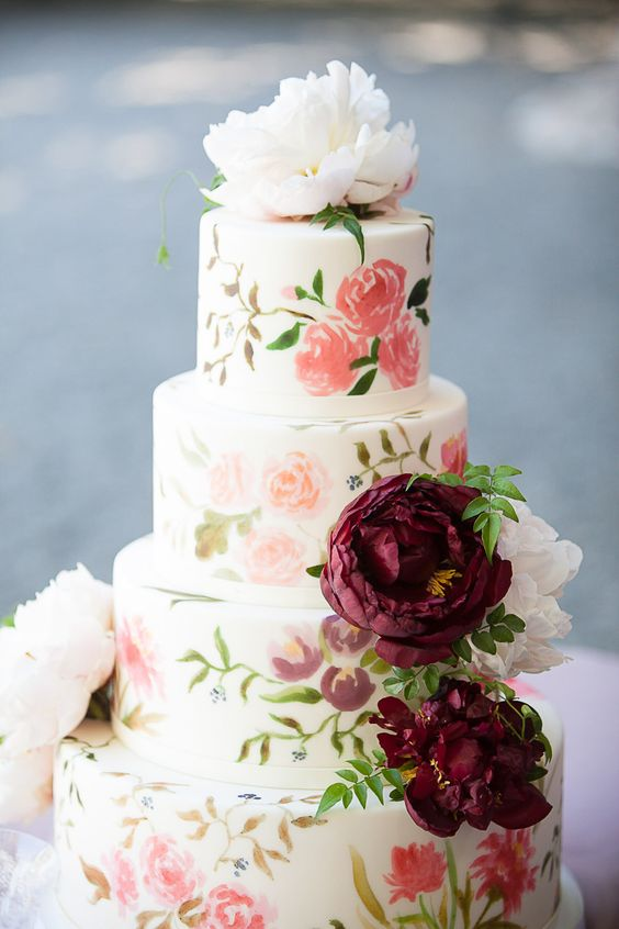 a sweet pastel handpainted wedding cake in various subtle shades with fresh blooms on top is ideal for summer