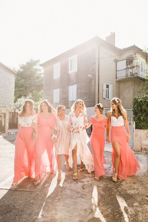 bridesmaids wearing mismatching outfits - coral dresses and floral bodices and coral skirts look very bold and trendy