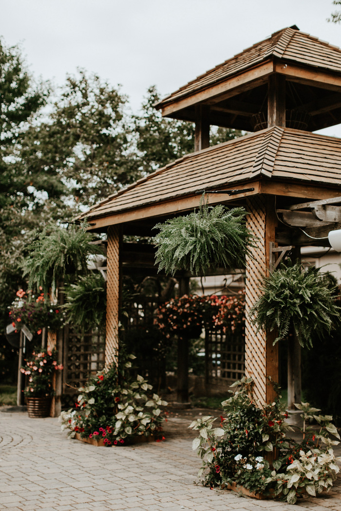 A large gazebo was decorated with lush ferns, red and white blooms and fresh greenery