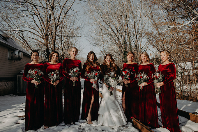 The bridesmaids were wearing burgundy velvet maxi gowns with long sleeves and high necklines