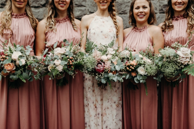 The bridesmaids were wearing pink draped halter neckline dresses, the maid of honor was rocking a floral halter neckline dress