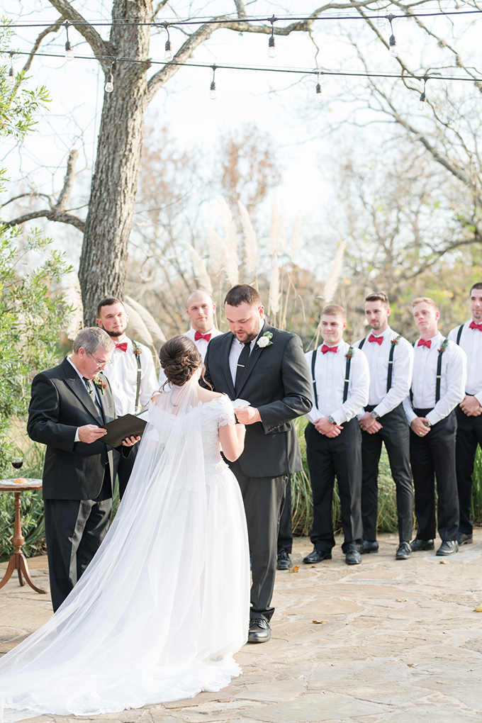 The groom was wearing a black suit with a tie and the groomsmen were rocking black pants, suspenders and red bow ties