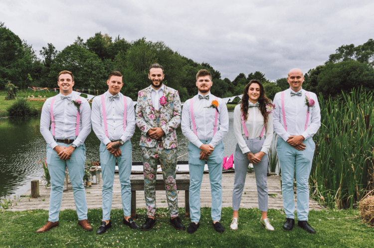 The groomsmen were rocking blue pants, pink suspenders, floral bow ties and white shirts