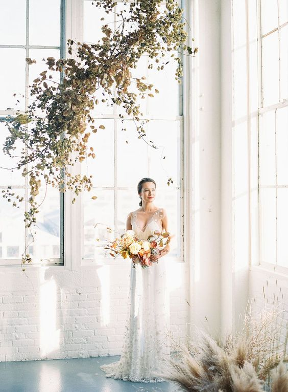 a minimalist wedding ceremony space indoors done with pampas grass and dried herbs and leaves