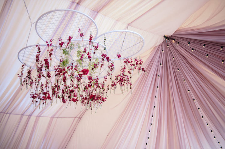 Bright florals with greenery were hanging down from embroidery hoops and there were many lights