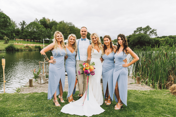 The bridesmaids were rocking powder blue wrap midi dresses, and the bridesman was wearing neutral pants, blue suspenders and a bow tie