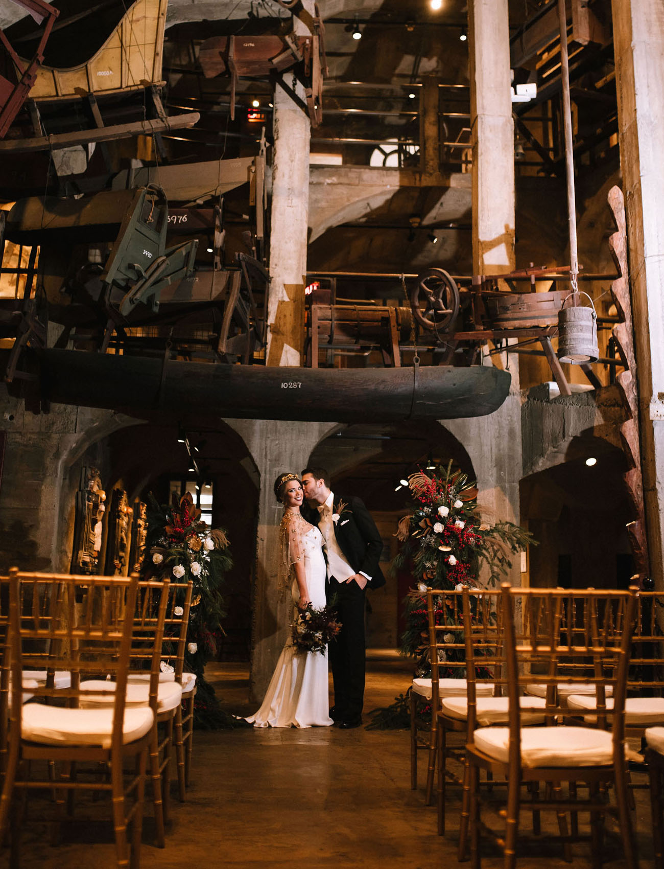 The wedding ceremony took place in the museum hall, with lush florals and evergreens