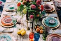 07 a bright Mediterranean table setting with colored glasses and plates and chargers plus lush florals