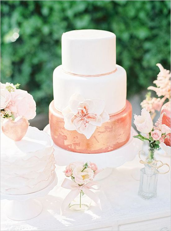 a cool and bold wedding cake with white tiers and a coral and gold tier plus a sugar bloom