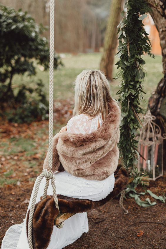 a large and comfy camel fur coat is a great idea to cover up for a winter boho bride