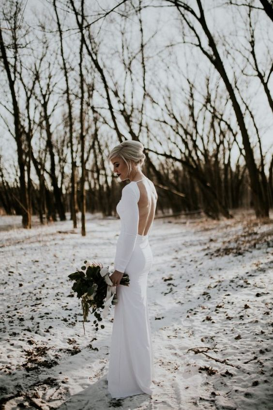 a minimalist fitting wedding gown with a high neckline and an open back for a stylish and sexy statement