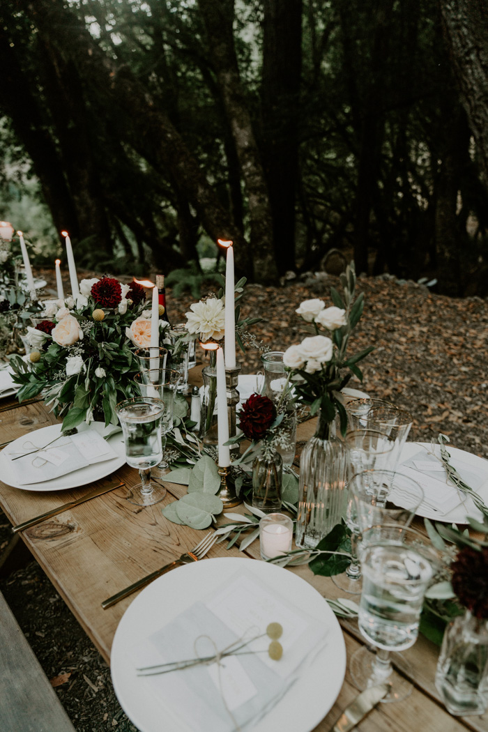 The table settings were done with tall candles, with uncovered tables and lots of greenery and blooms
