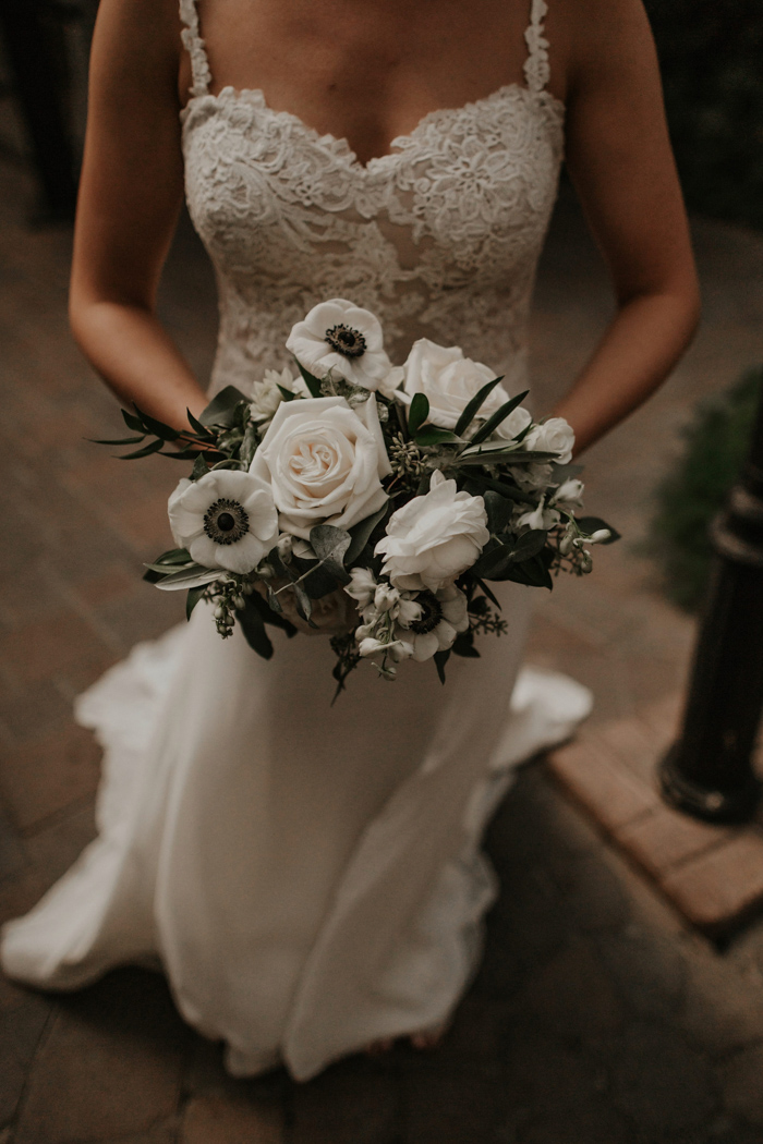 The wedding bouquets were made of pale greenery and white anemones and roses