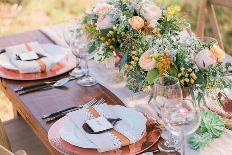 a beautiful wedding tablescape with hammered copper chargers and lush floral centerpieces with blush and peachy blooms