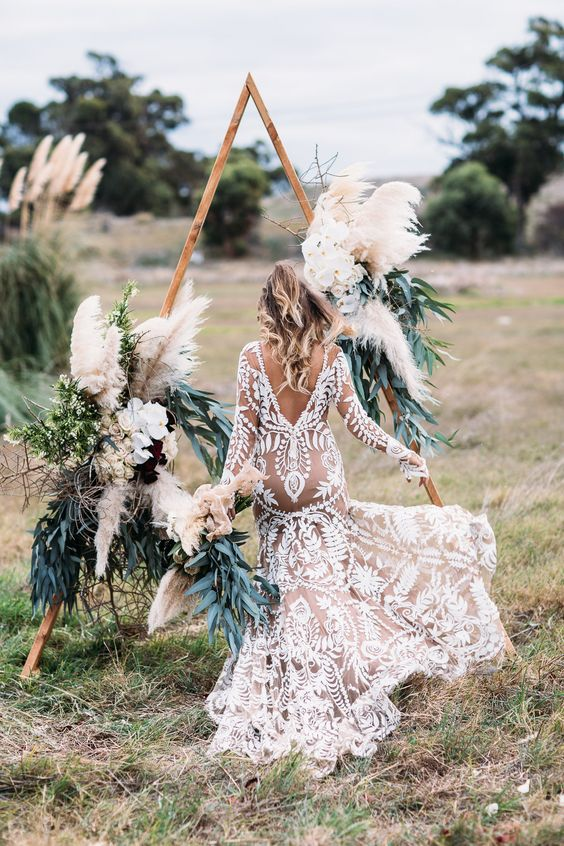 a boho chic triangular wedding arch decorated with pampas grass, greenery and lush florals